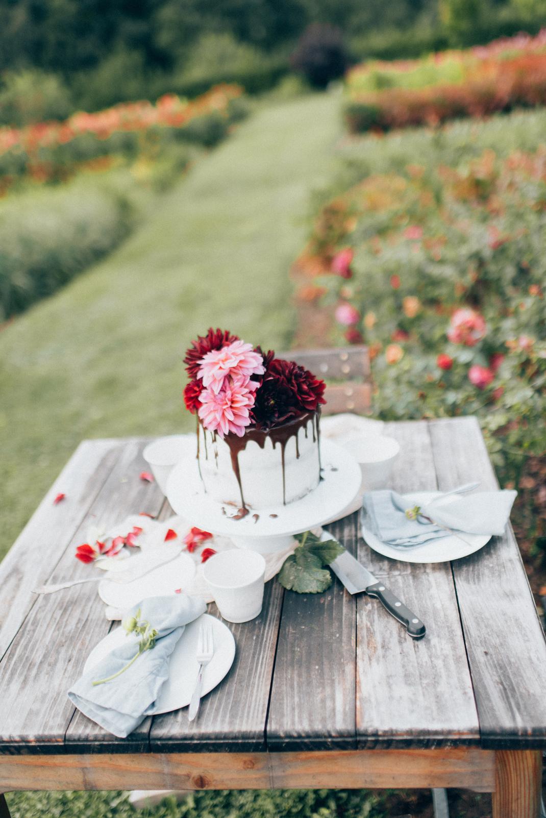 Silvia Fischer. Echte Kuchenliebe. Torte auf Tisch im Blumengarten